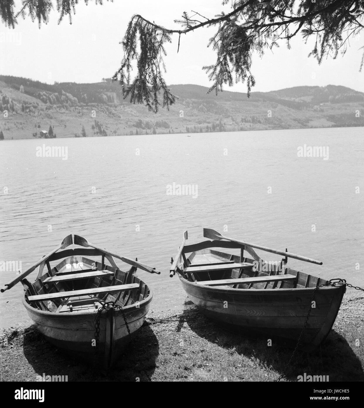 Two wooden boats parked on shoreline by lake. - Stock Image