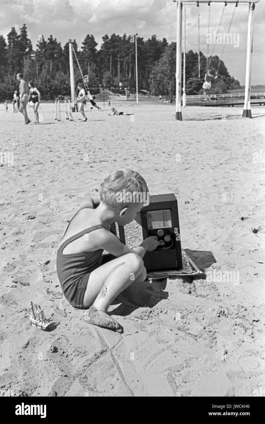 Little boy changing channel on radio on beach. - Stock Image