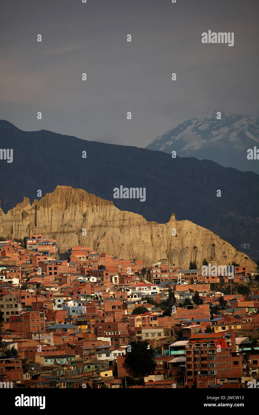 Brick houses, eroded hill and Illimani (6438m/21,122ft), La Paz, Bolivia, South America - Stock Image