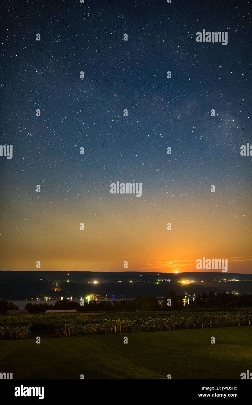 Moon rising over vinyard and lake under stars and milky way Stock Photo