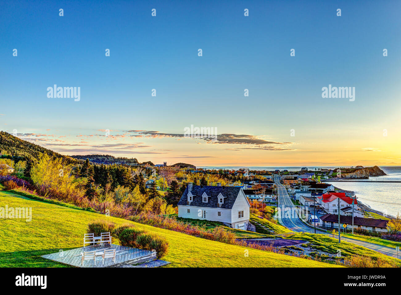 Hotel chairs on hill during sunrise in Perce, Gaspe Peninsula, Quebec, Canada, Gaspesie region with cityscape - Stock Image