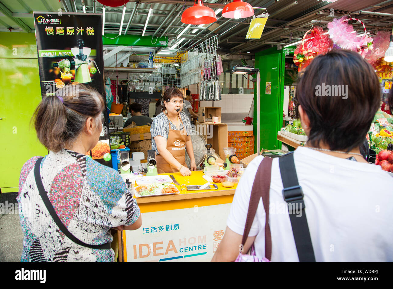 HONG KONG - JULY 10, 2017: A street vendor making a sales pitch on her kitchenware in Mong Kok. The area is a popular street market where visitors go  - Stock Image