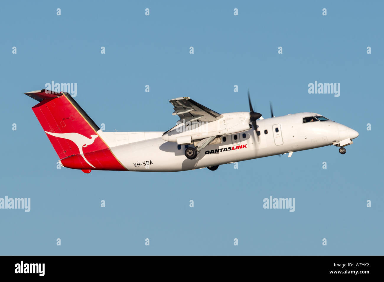 QantasLink (Qantas) deHavilland DHC-8 (Dash 8) twin engined regional airliner aircraft departing Sydney Airport. Stock Photo
