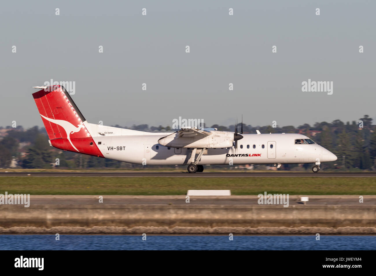 QantasLink (Qantas) deHavilland DHC-8 (Dash 8) twin engined regional airliner aircraft departing Sydney Airport. Stock Photo