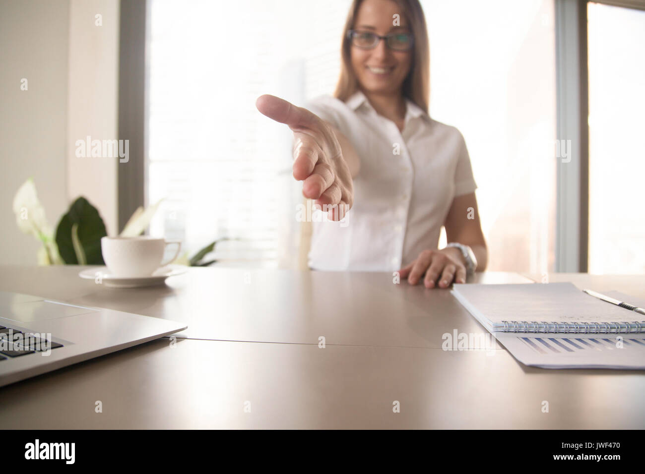 Smiling businesswoman reaching out hand at camera for welcoming  - Stock Image