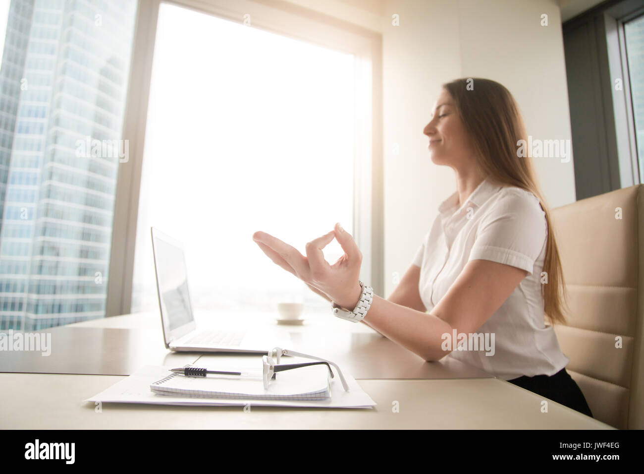 Calm peaceful businesswoman practicing yoga at work, meditating  - Stock Image