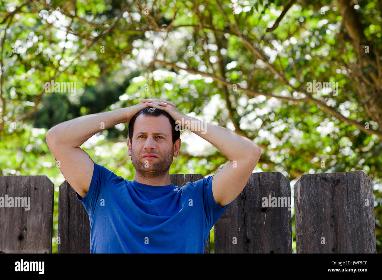 Man with his hand on his head outdoors curious about what the New Year will hold for him. - Stock Image