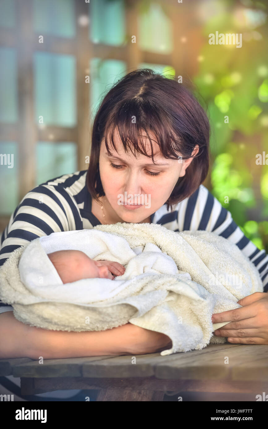 loving mother bends over the baby. Summer portrait in the garden - Stock Image