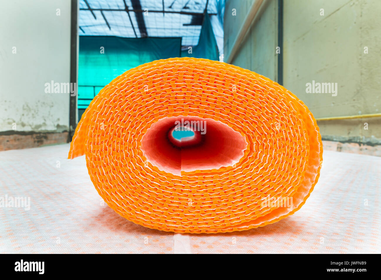 Orange roll of membrane waterproofing, separation and steam escape.  Drainage system for floor of terrace - roof, with fiber fabric - Stock Image