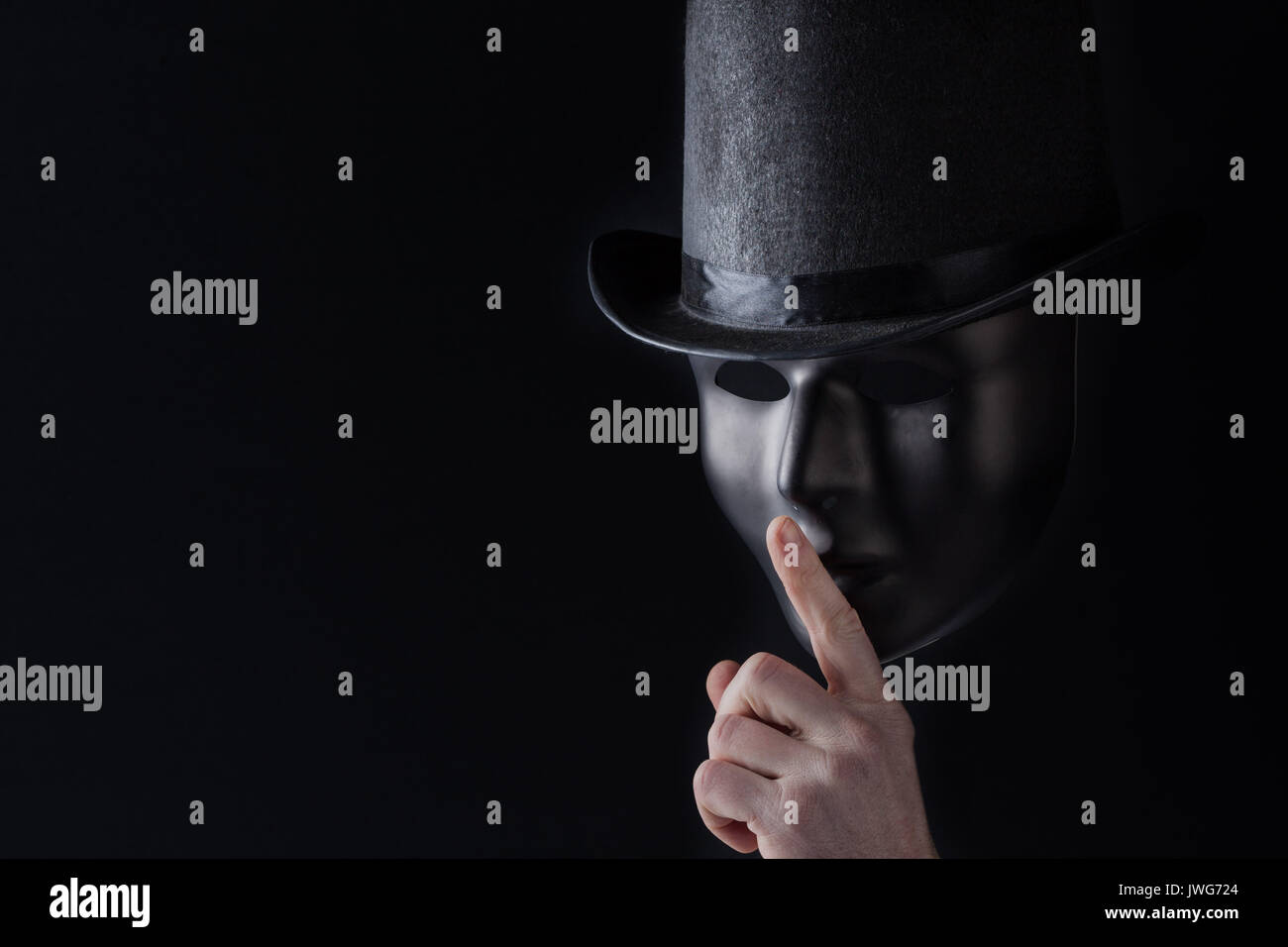 Male finger showing shh sign on black mask wearing black top hat on black background with copy space. Freedom of speech and silence concept - Stock Image