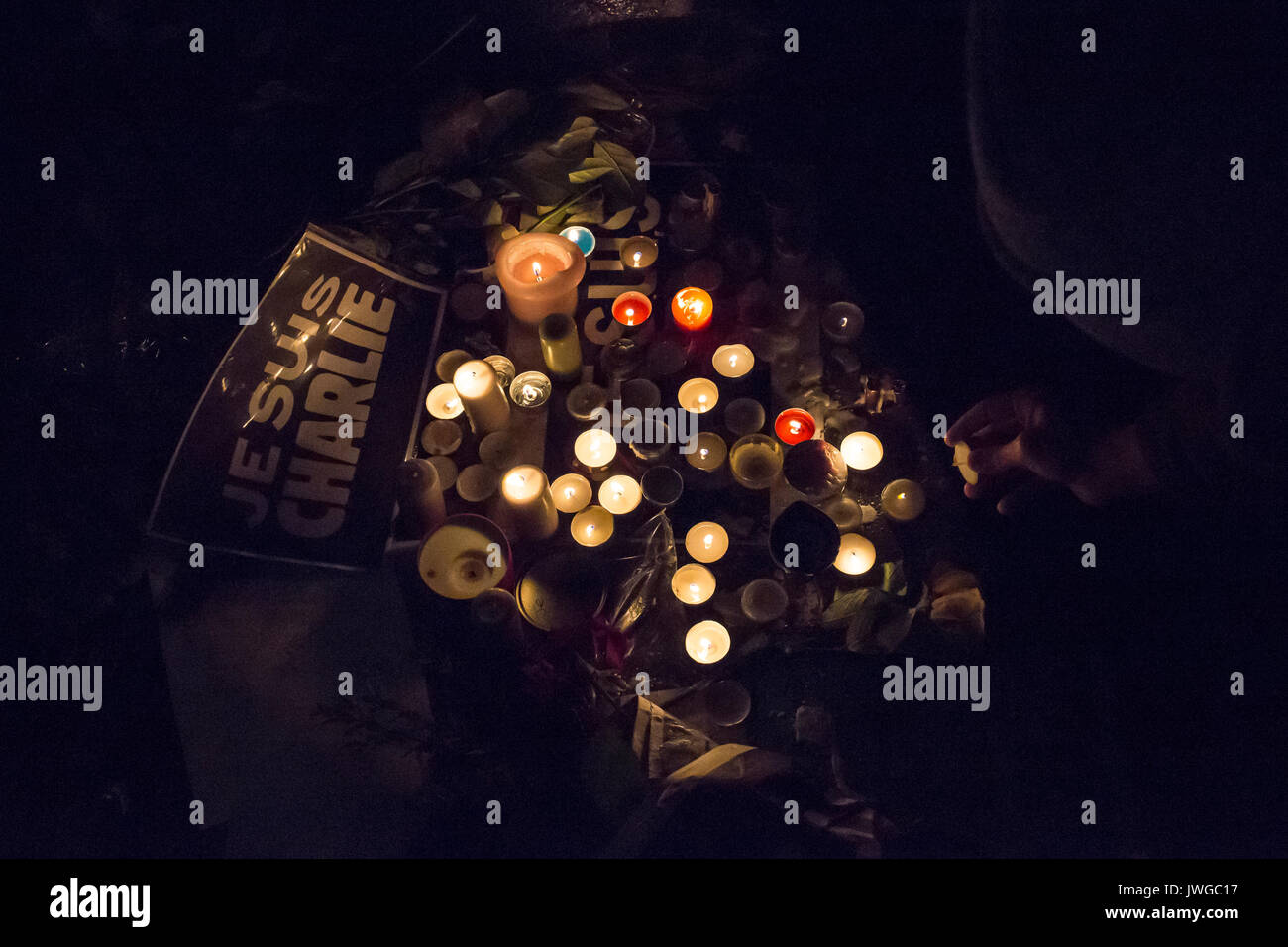 je suis charlie sign among candles. Homage at the victims of Charlie hebdo killing in Paris the 7th of january 2015. - Stock Image