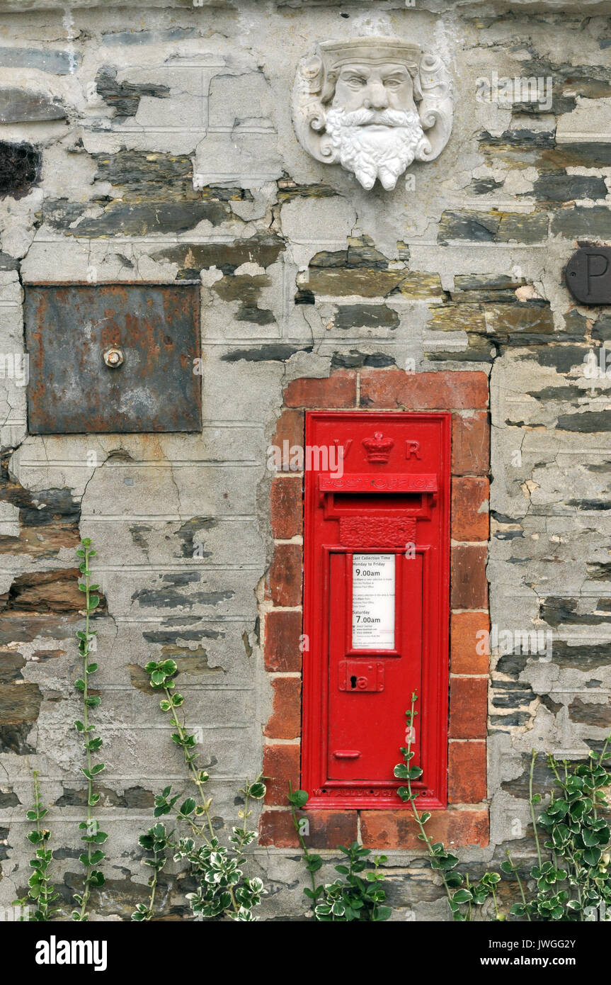An old fashioned metal posting box set into a wall with a stonework or antique mask or gargoyle above it in Padstow, North Cornwall - Stock Image