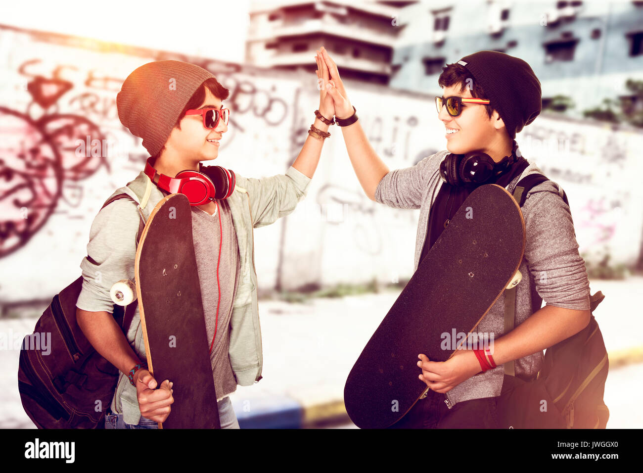 Happy teen boys outdoors, two stylish teenagers with skateboards in hands saluting each other, modern lifestyle, hipster culture, active summer holida - Stock Image