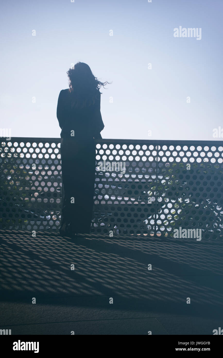 Rear view silhouette of a young woman standing outdoors - Stock Image