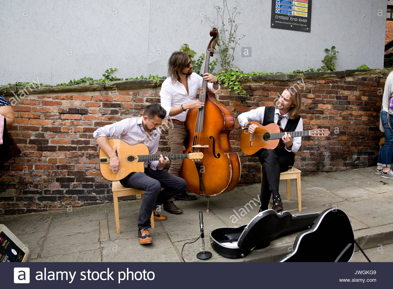 The Djanco Gypsy Jazz Trio giving a free street gig at the Lincoln 40's Festival, Lincolnshire, UK. - Stock Image