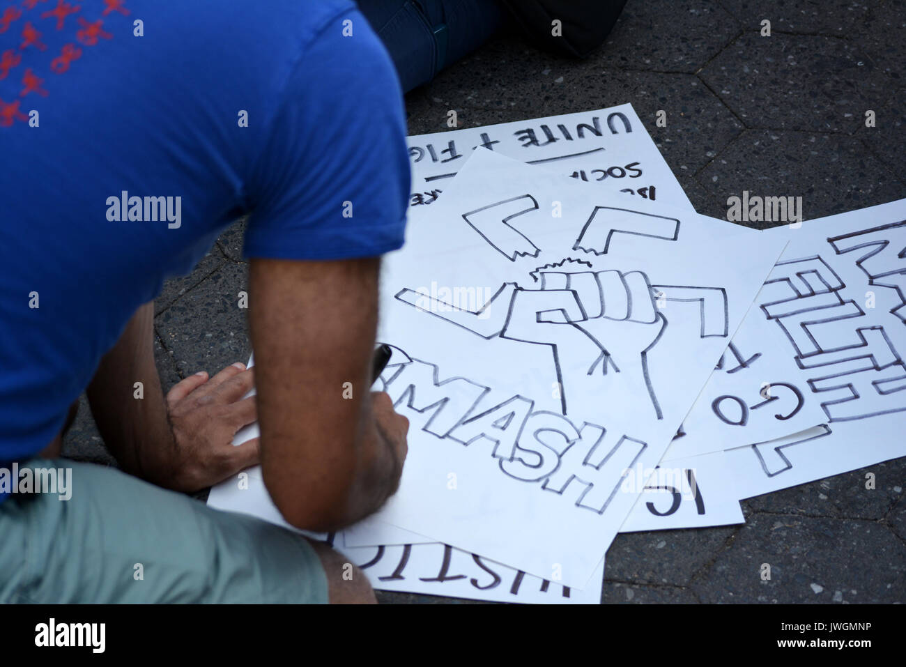 Protester making signs at a rally in Union Square in Manhattan to denounce neo-nazi violence in Charlottesville, Virginia and President Trump. - Stock Image