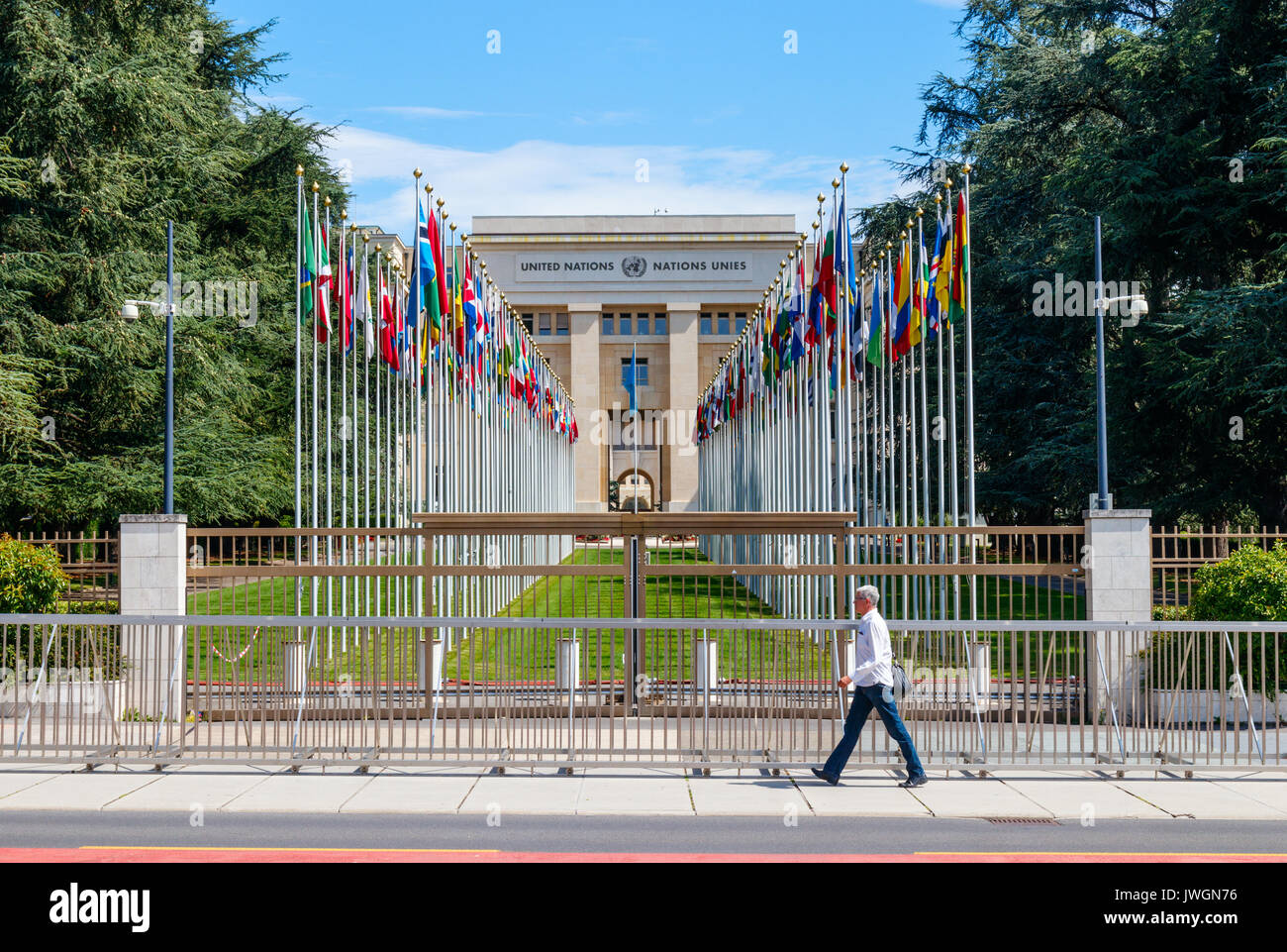 Passerby on Place des Nations (Square of the Nations) with on the background the Allee des Nations. Geneva, Switzerland. - Stock Image