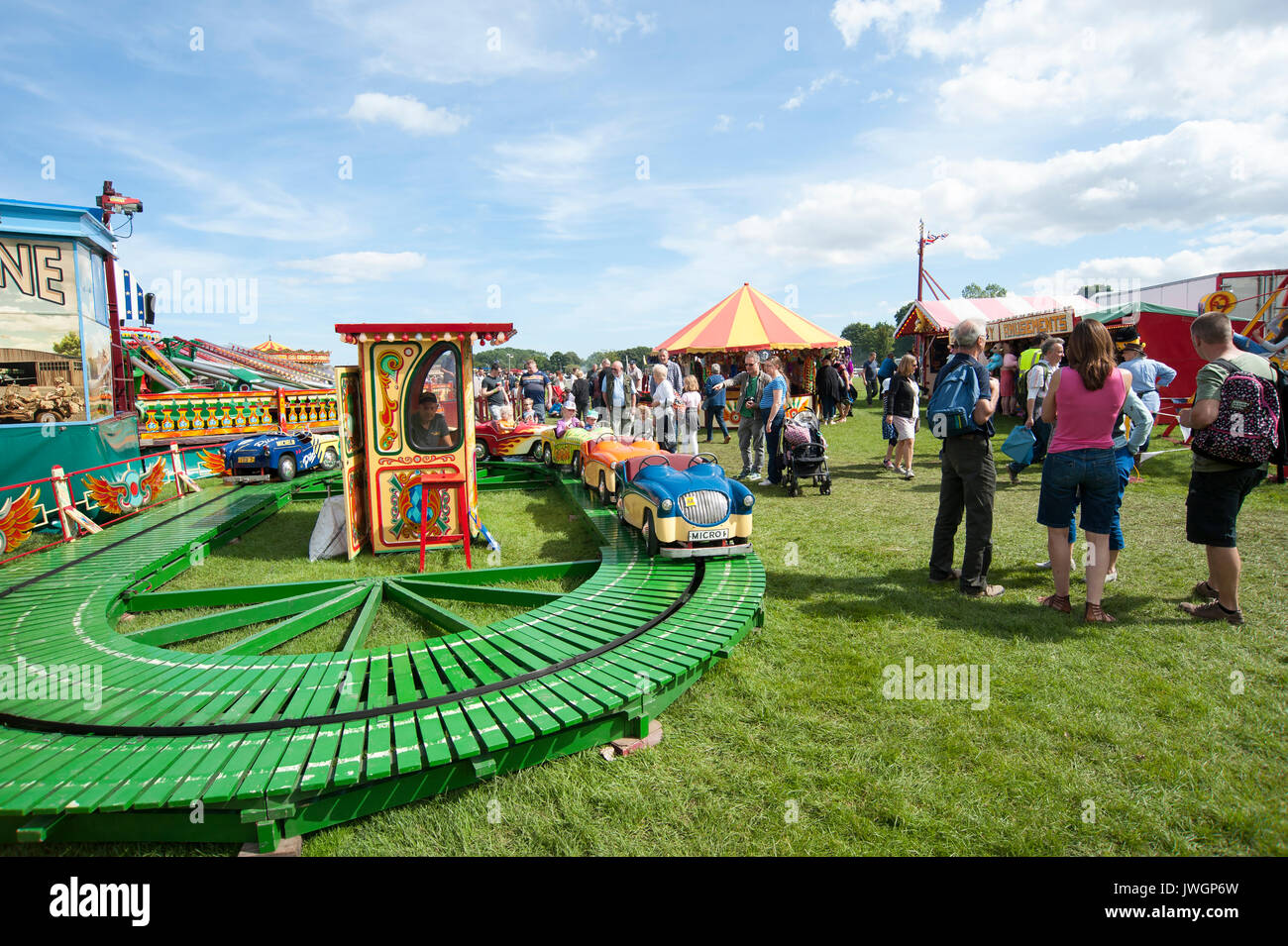 Families enjoying a day out in the sunshine at a children's funfair at Vintage steam rally, UK GB England Stock Photo