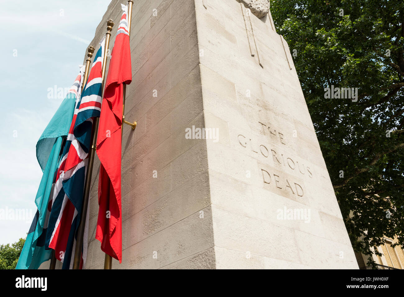 Flags flanking the sides of The Cenotaph representing the Royal Navy, the British Army, the Royal Air Force, and the Merchant Navy. - Stock Image
