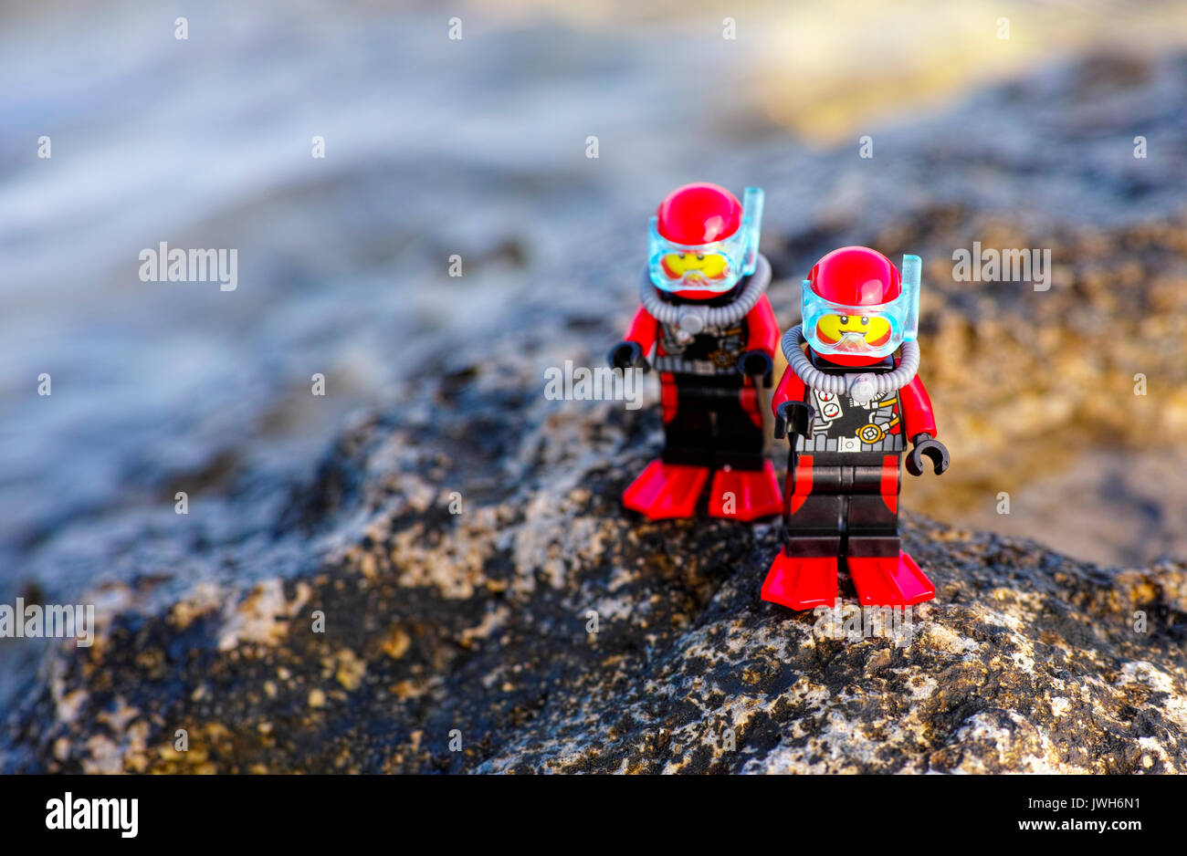 Paphos, Cyprus - October 09, 2016 Two Lego scuba divers minifigures standing on sea rock. - Stock Image