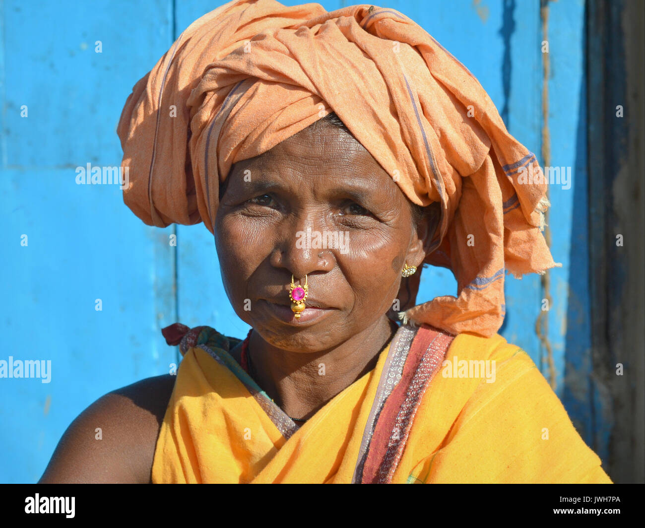 Closeup street portrait (outdoor headshot, seven-eighths view) of a mature Indian Adivasi market woman with gold - Stock Image