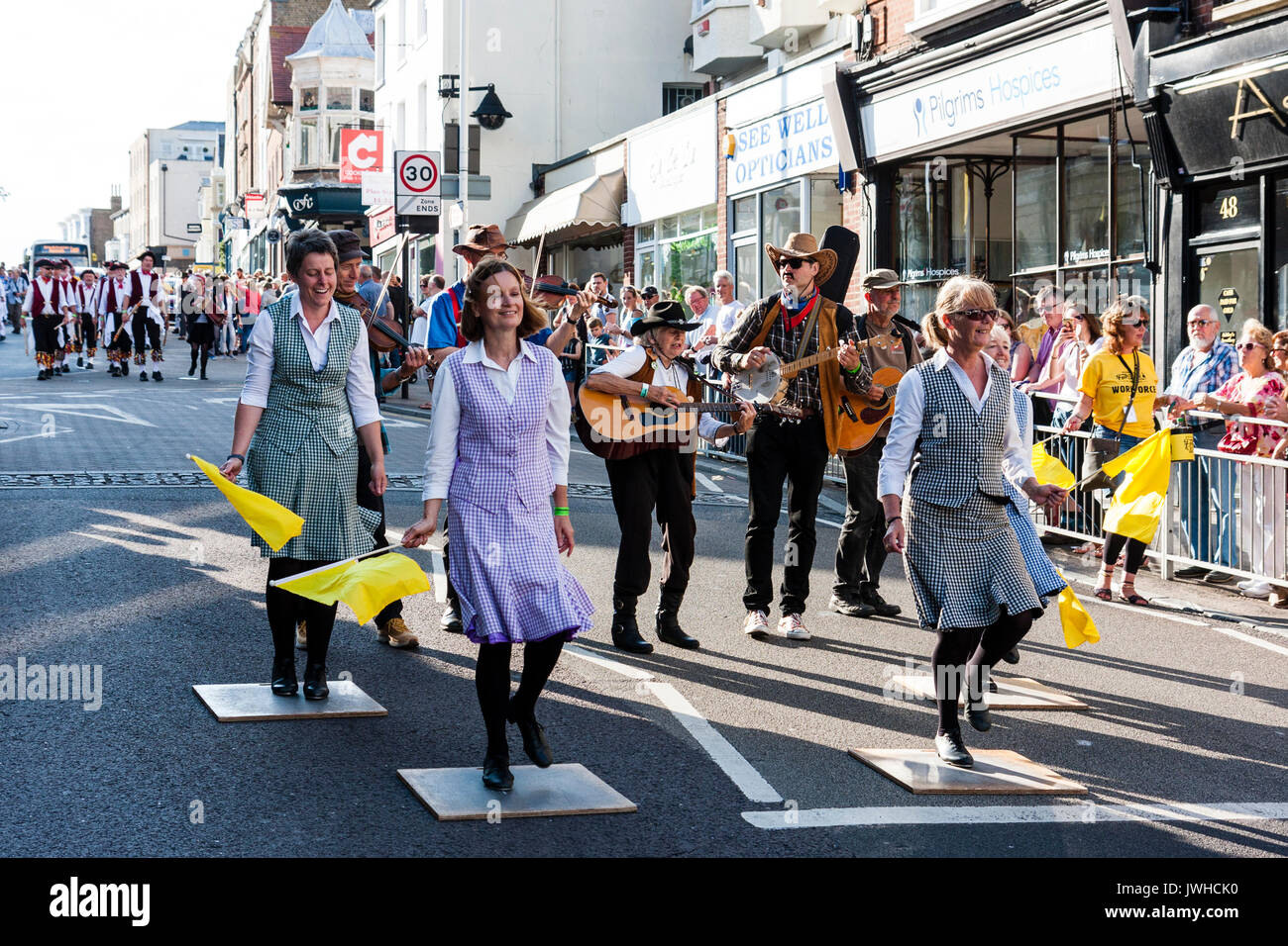 Broadstairs Folk week festival parade. Tap and Sync womens Morris dancers dancing in the High street  while waving yellow hankies.Parade in background, people watching on pavement. - Stock Image