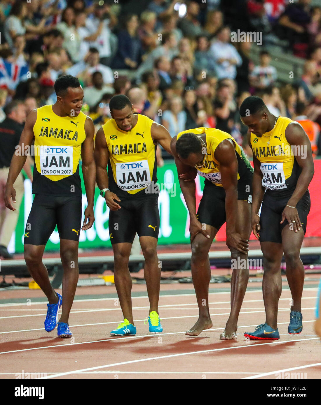 London, UK. 12th Aug, 2017. London, August 12 2017 . Usain Bolt stops in agony as he leaves the track with his Jamaican teammates after injuring his hamstring in the final leg of the men's 4x 100m relay on day nine of the IAAF London 2017 world Championships at the London Stadium. Credit: Paul Davey/Alamy Live News - Stock Image