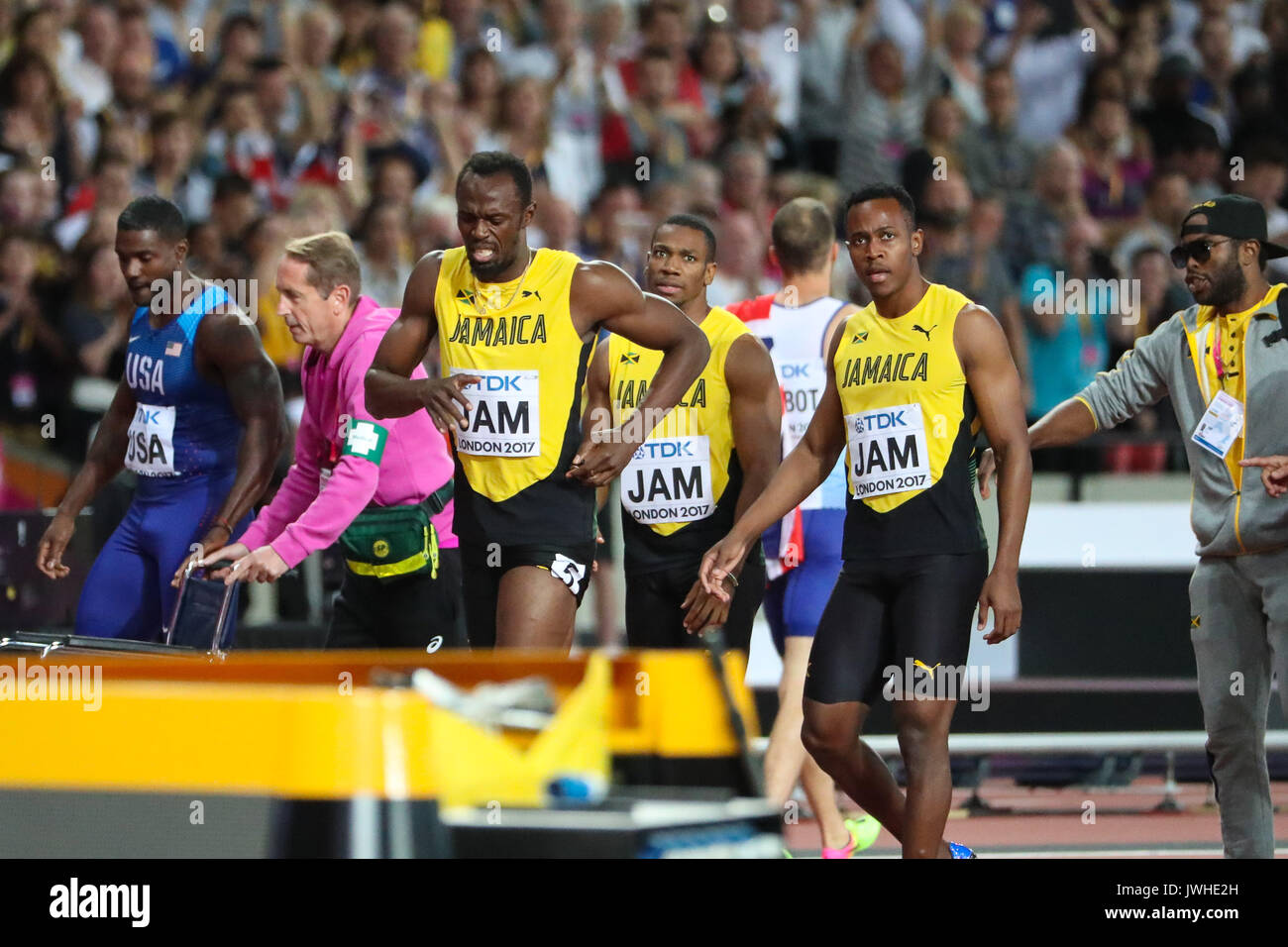 London, UK. 12th Aug, 2017. London, August 12 2017 . Usai Bolt crosses the finish line assisted by his teammates after suffering an injury to his hamstring as he ran the final 100m in the men's 4x 100m relay on day nine of the IAAF London 2017 world Championships at the London Stadium. Credit: Paul Davey/Alamy Live News - Stock Image