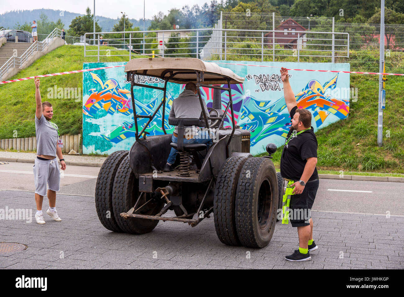 Bielsko-Biala, Poland. 12th Aug, 2017. International automotive trade fairs - MotoShow Bielsko-Biala. Man raising the red-white tape for the Lanz Bulldog tractor. Credit: Lukasz Obermann/Alamy Live News - Stock Image