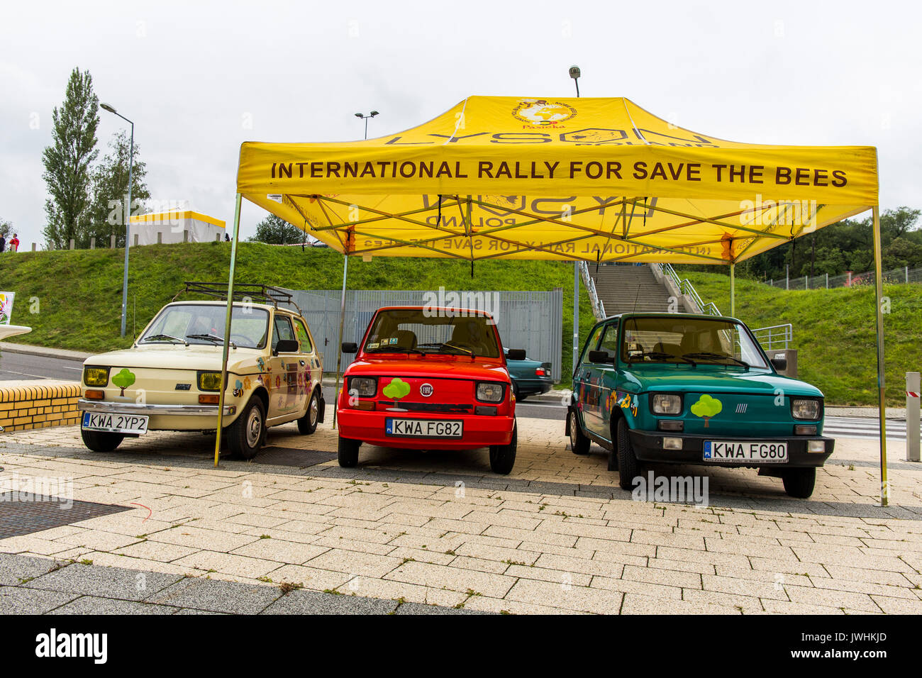 Bielsko-Biala, Poland. 12th Aug, 2017. International automotive trade fairs - MotoShow Bielsko-Biala. Three fiat 126p (polish - maluch) painted in flowers parked under yellow umbrella and promoting an international rally for save the bees. Credit: Lukasz Obermann/Alamy Live News - Stock Image