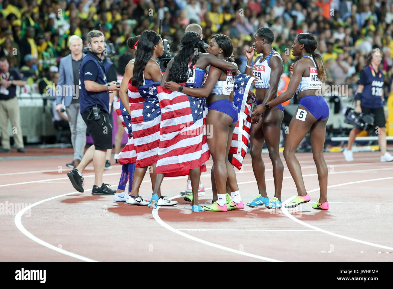 Team USA  and Team BG celebrate their victory in the women's 4x100m relay on day nine of the IAAF London 2017 world Championships at the London Stadium. © Paul Davey. - Stock Image