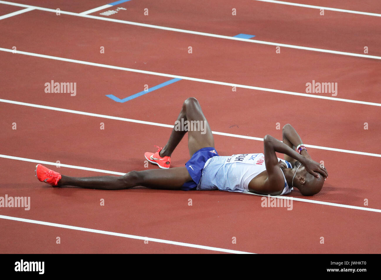 London, UK. 12th Aug, 2017.  an exhausted Mo Farah, Great Britain, lies on the track after winning silver in the men's 5000m final on day nine of the IAAF London 2017 world Championships at the London Stadium. Credit: Paul Davey/Alamy Live News - Stock Image