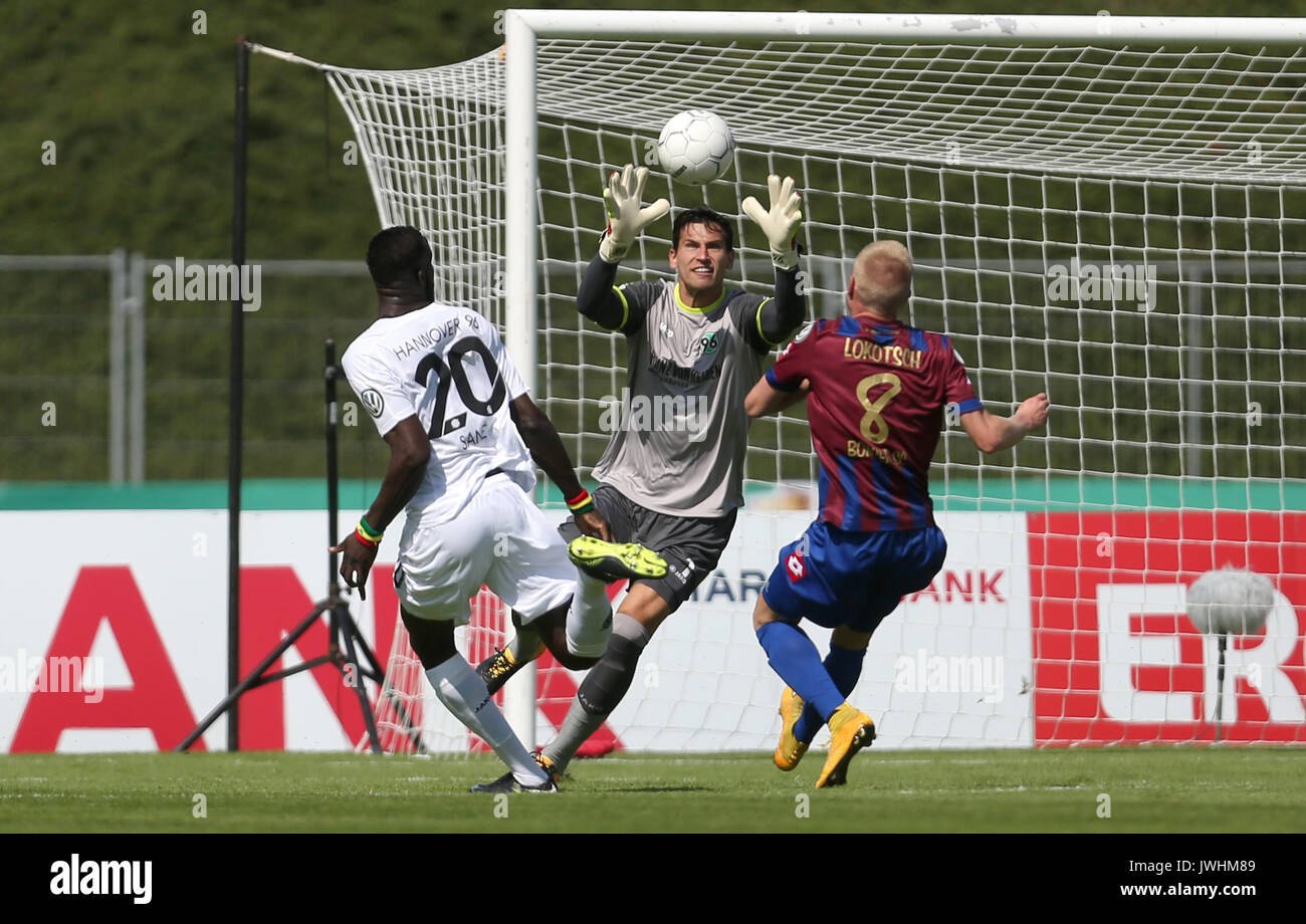 Hanover's Salif Sane (L) and goalkeeper Philipp Tschauner (C) attempt to keep Bonn's Lars Lokotsch from the ball during the German Soccer Association (DFB) Cup first-round match between Bonner SC and Hanover 96 in the Sportpark Nord Stadium in Bonn, Germany, 13 August 2017. (EMBARGO CONDITIONS - ATTENTION: The DFB prohibits the utilisation and publication of sequential pictures on the internet and other online media during the match (including half-time). ATTENTION: BLOCKING PERIOD! The DFB permits the further utilisation and publication of the pictures for mobile services (especially MMS) - Stock Image