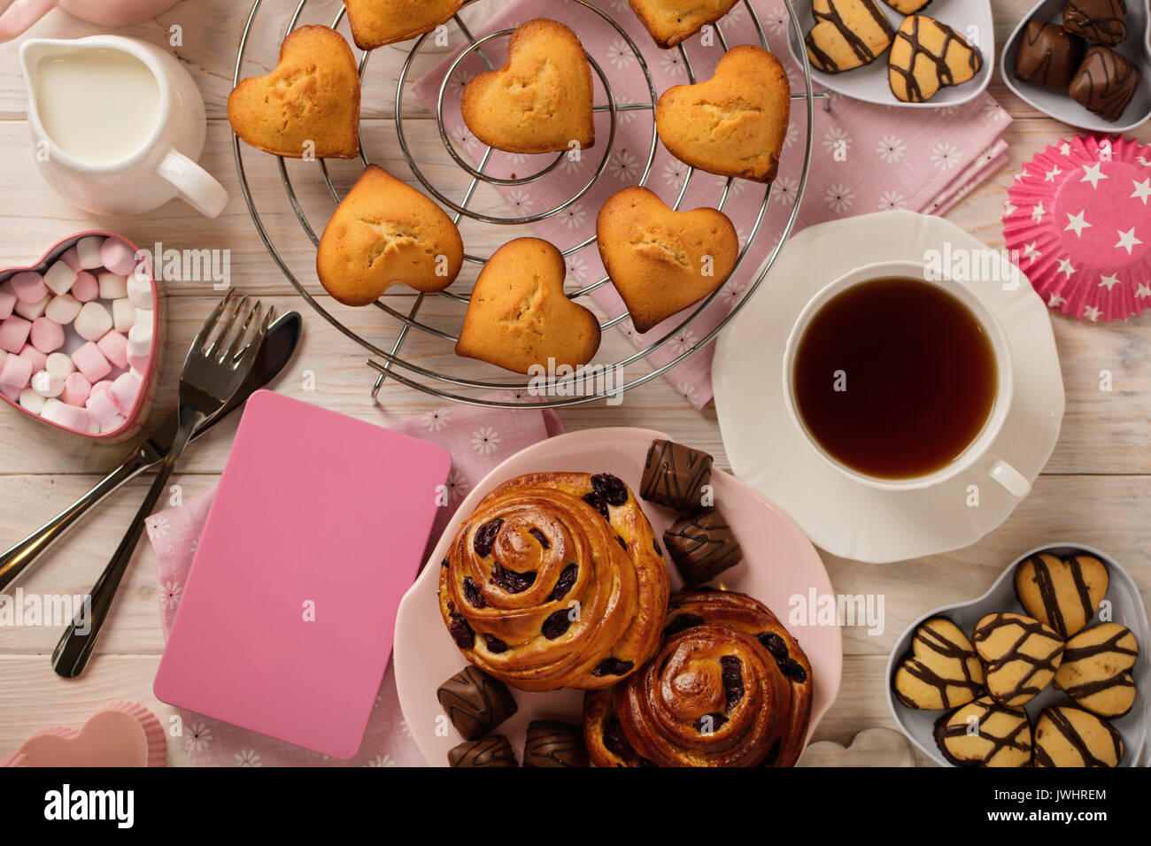 Flat lay cakes and cookies, muffins and rolls, biscuits and sweets, tea and coffee with marshmallow. Top view. - Stock Image