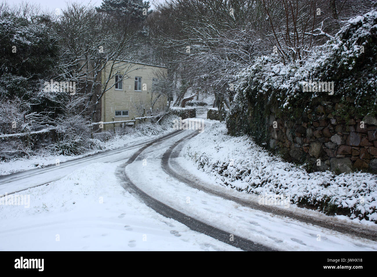 British Channel Islands. Alderney. Winter scene of cottage and snow-covered country lane. - Stock Image