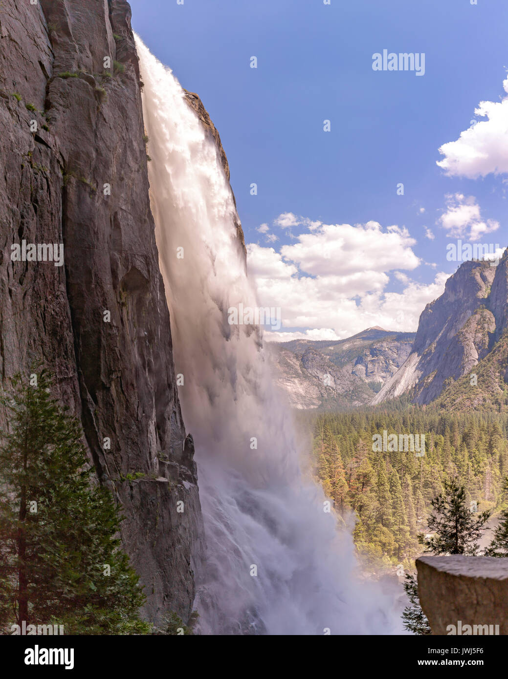Yosemite Falls up close and shot from a unique angle in a wet area. Lower Falls in Yosemite with a view of the valley in the background - Stock Image
