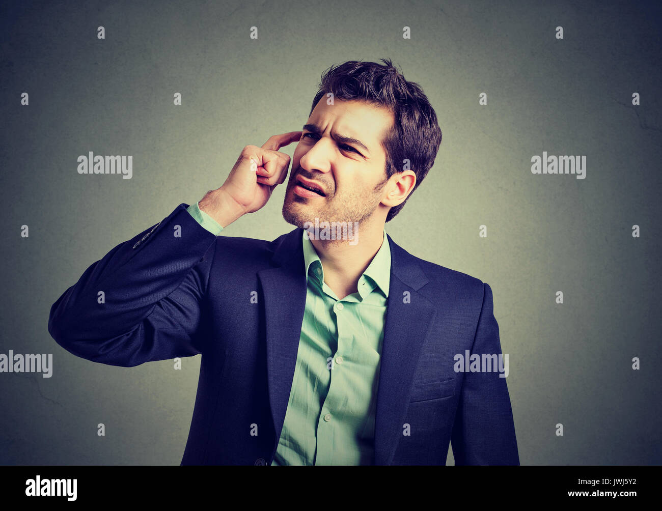 Confused business man thinking scratching his head - Stock Image