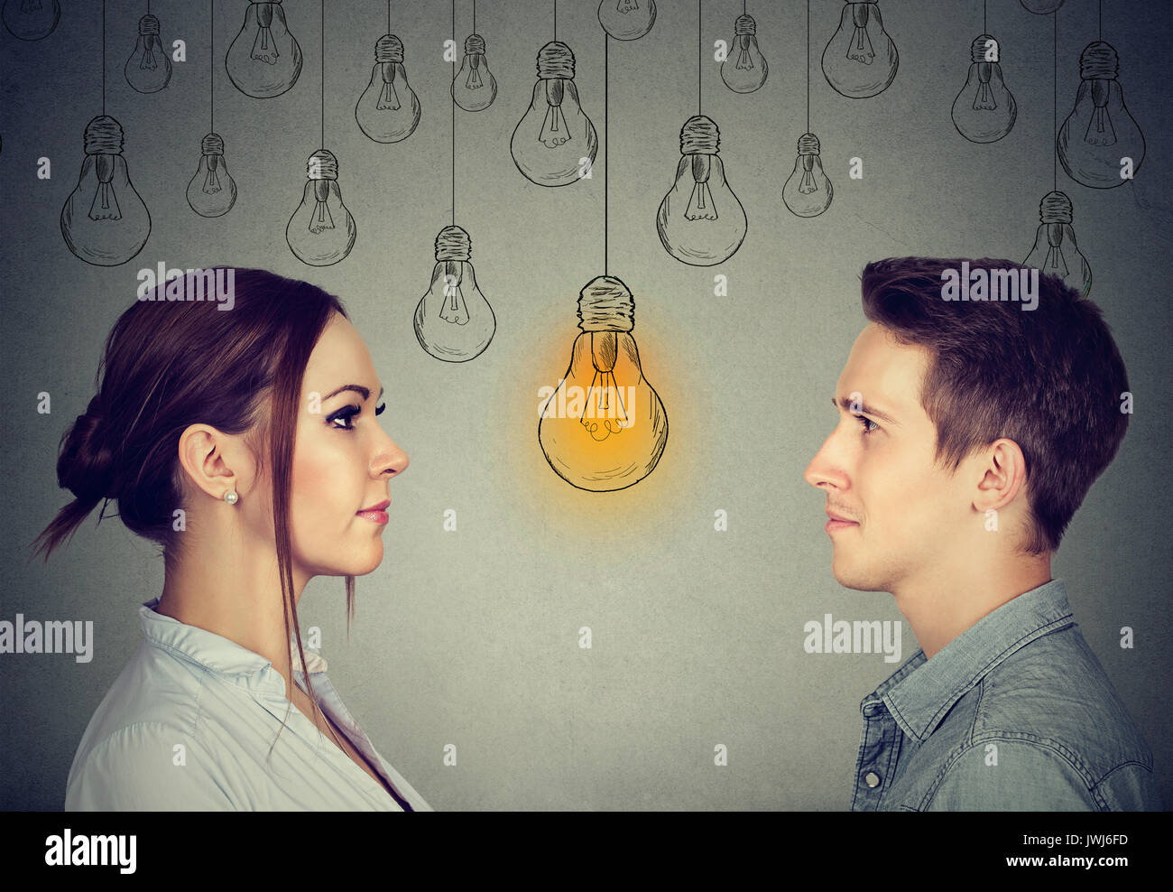 Cognitive skills ability concept, male vs female. Man and woman looking at bright light bulb isolated on gray wall background - Stock Image