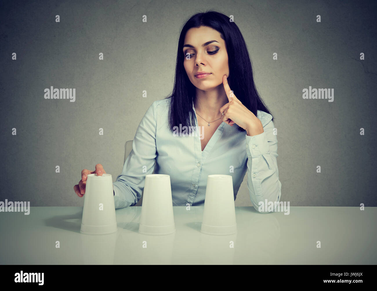 Young thoughtful woman playing a conjuring trick game - Stock Image