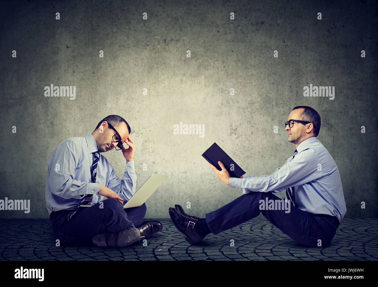 Computer versus book. Two men sitting on a floor one reading a book another working on laptop - Stock Image