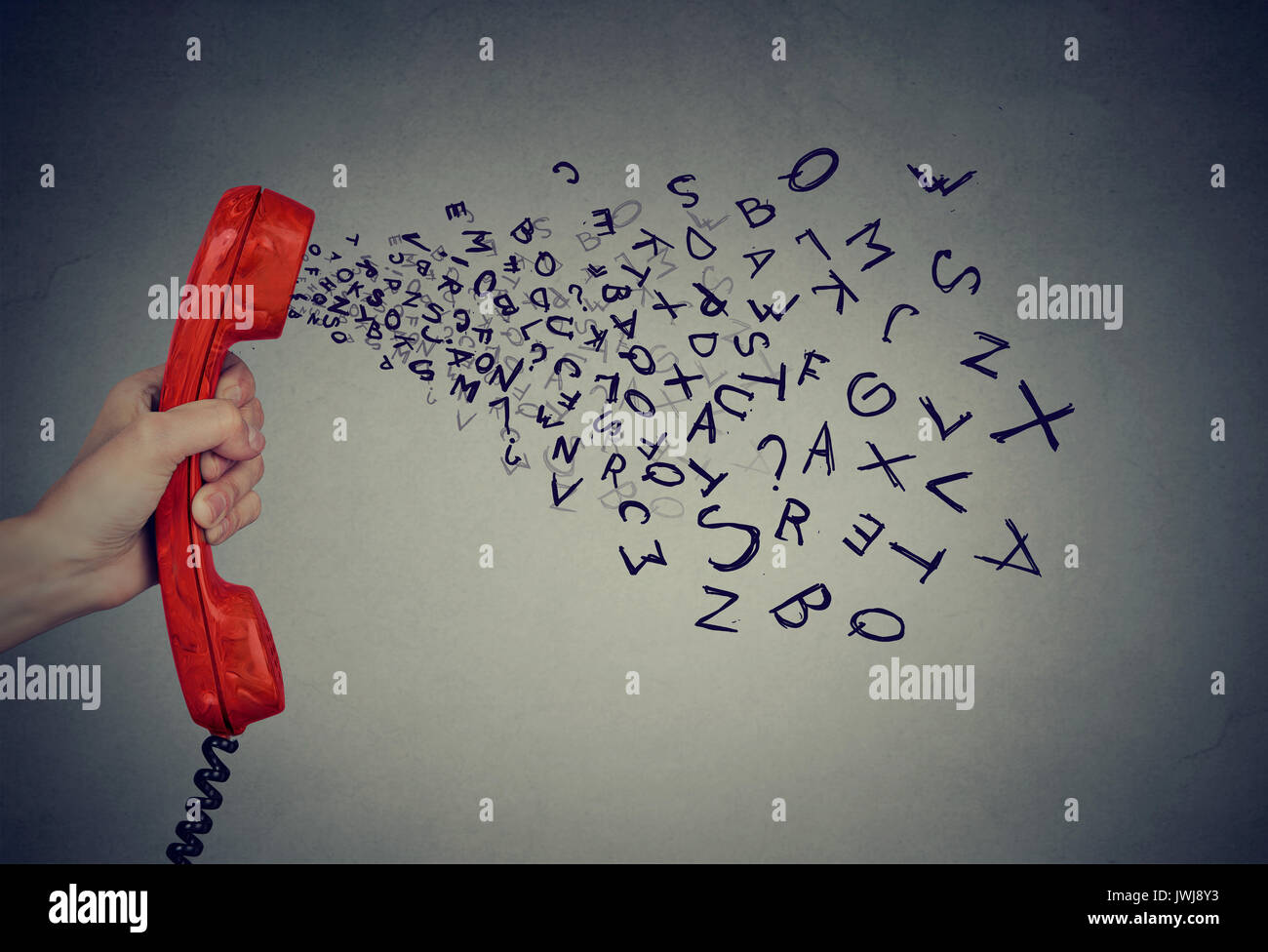 Hand holding telephone handset with alphabet letters coming out. Too many words during conversation concept - Stock Image