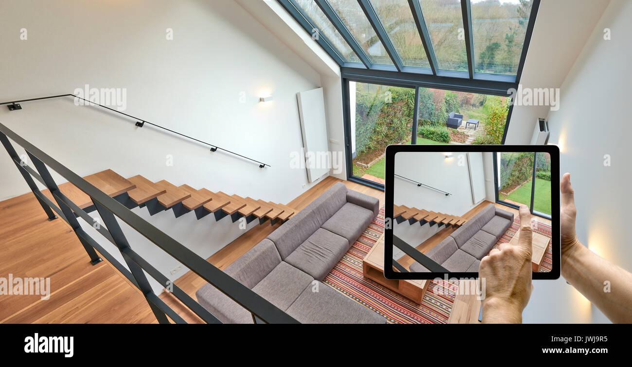 Mobile device with man hands taking picture in Modern living room with large windows and view on a automnal garden - Stock Image