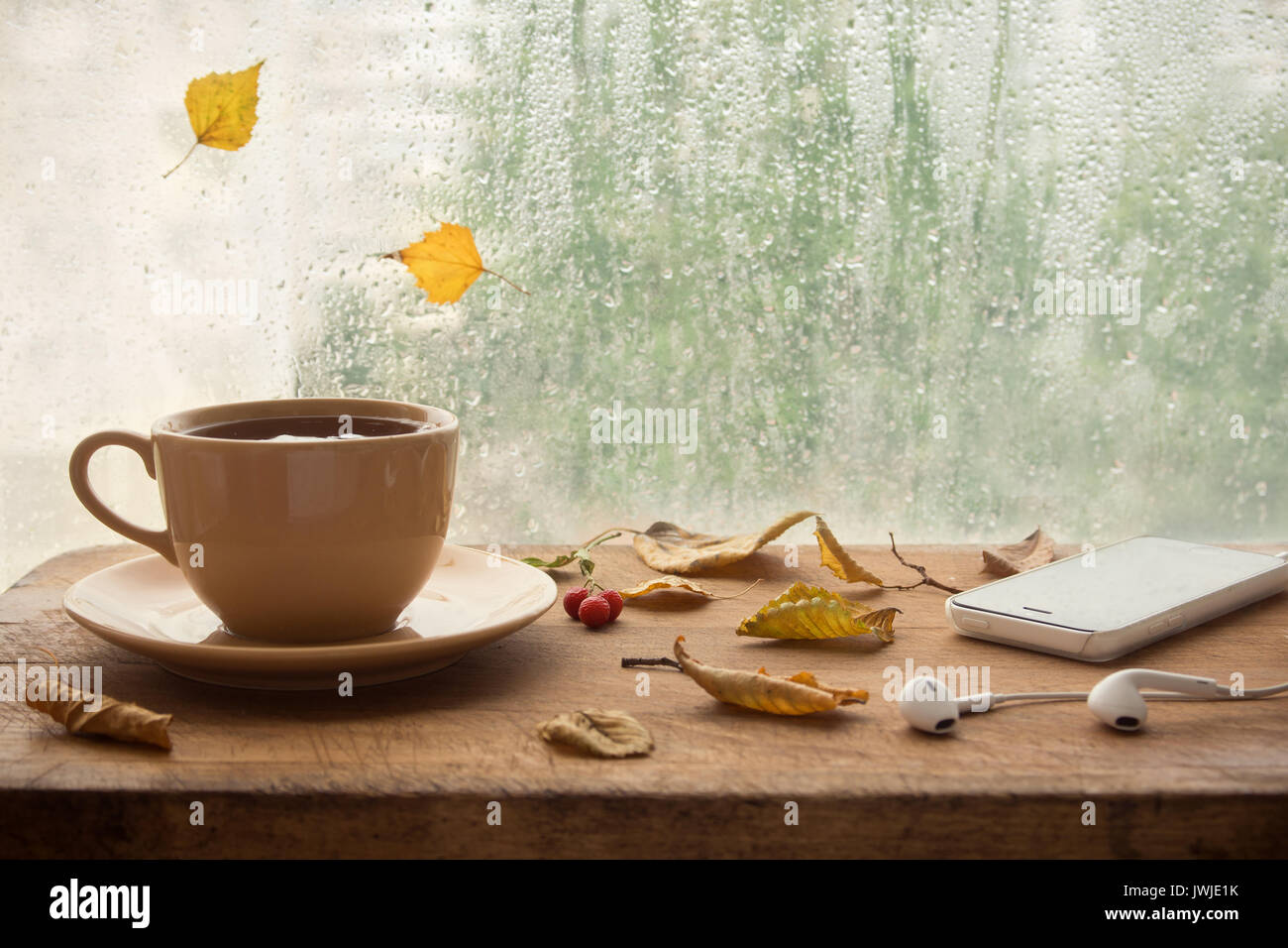 Cup of coffee or tea, smartphone and earbuds with autumn leaves near a window. Autumn playlist concept. Autumn music for rainy days. - Stock Image