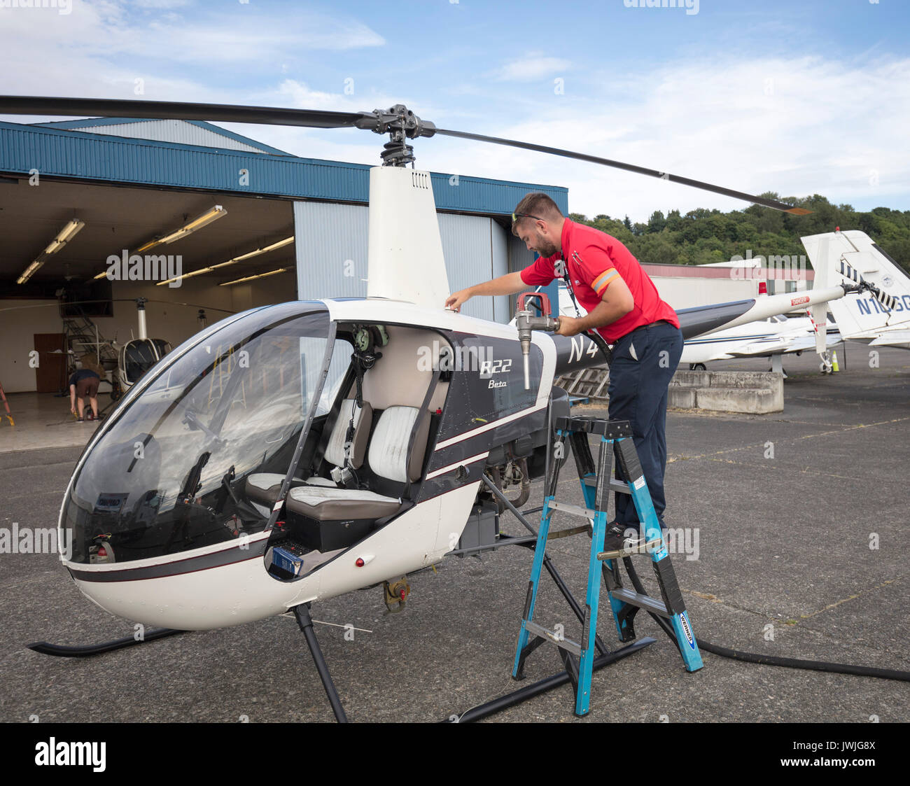 man refueling Robinson R22 helicopter, Boeing Field, Seattle, USA - Stock Image