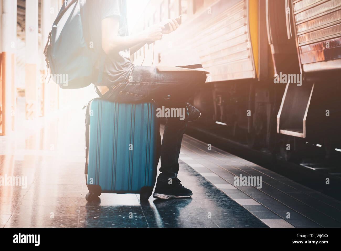 Backpacker listening musics from smartphone at the train station with a traveler. Travel concept. - Stock Image