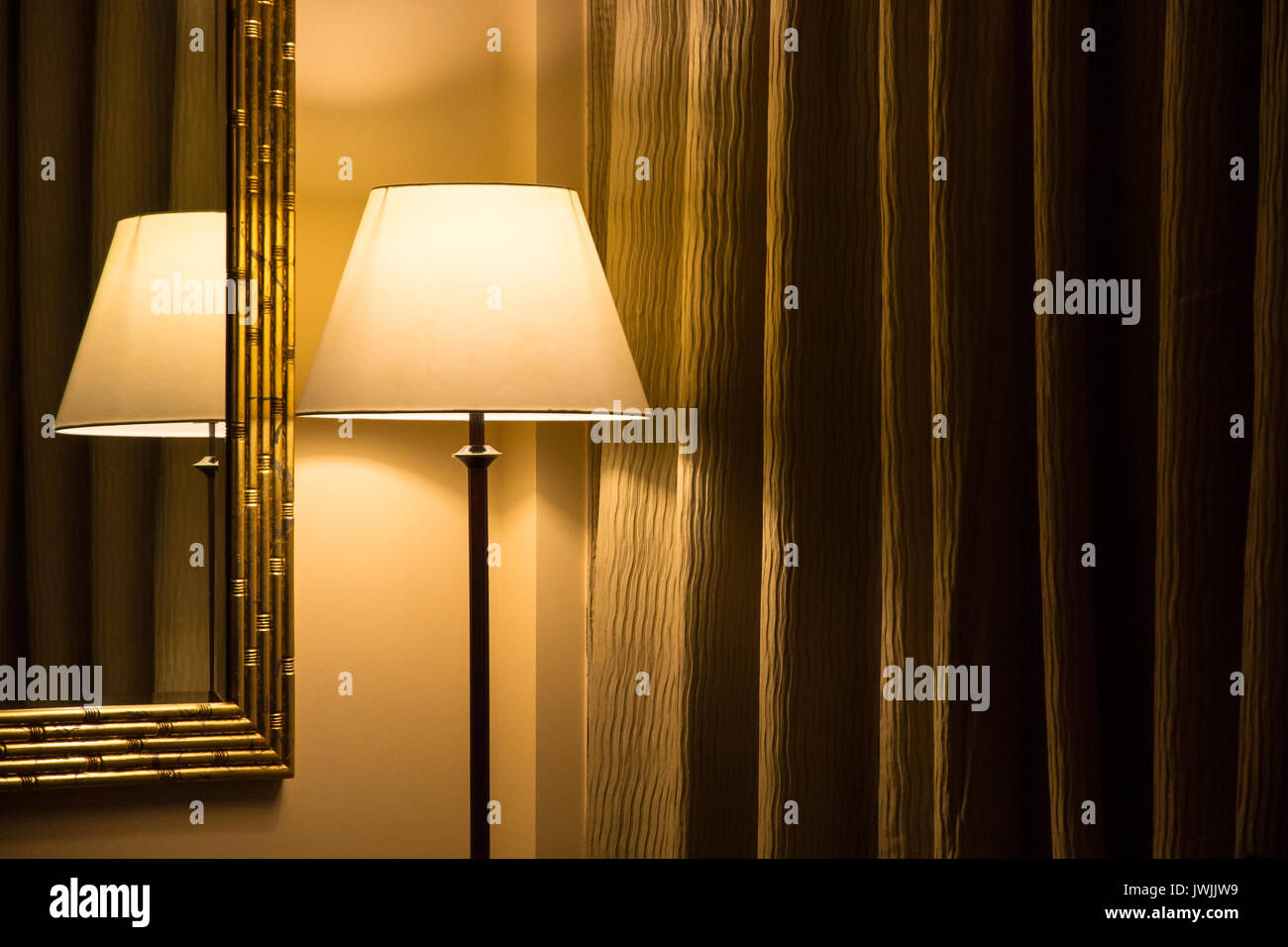 Standing Lamp And Reflection In A Mirror Of Hotel Room With Closed Dark Curtains Warm Incandescent Light Concept Anonymous Sterile Alone
