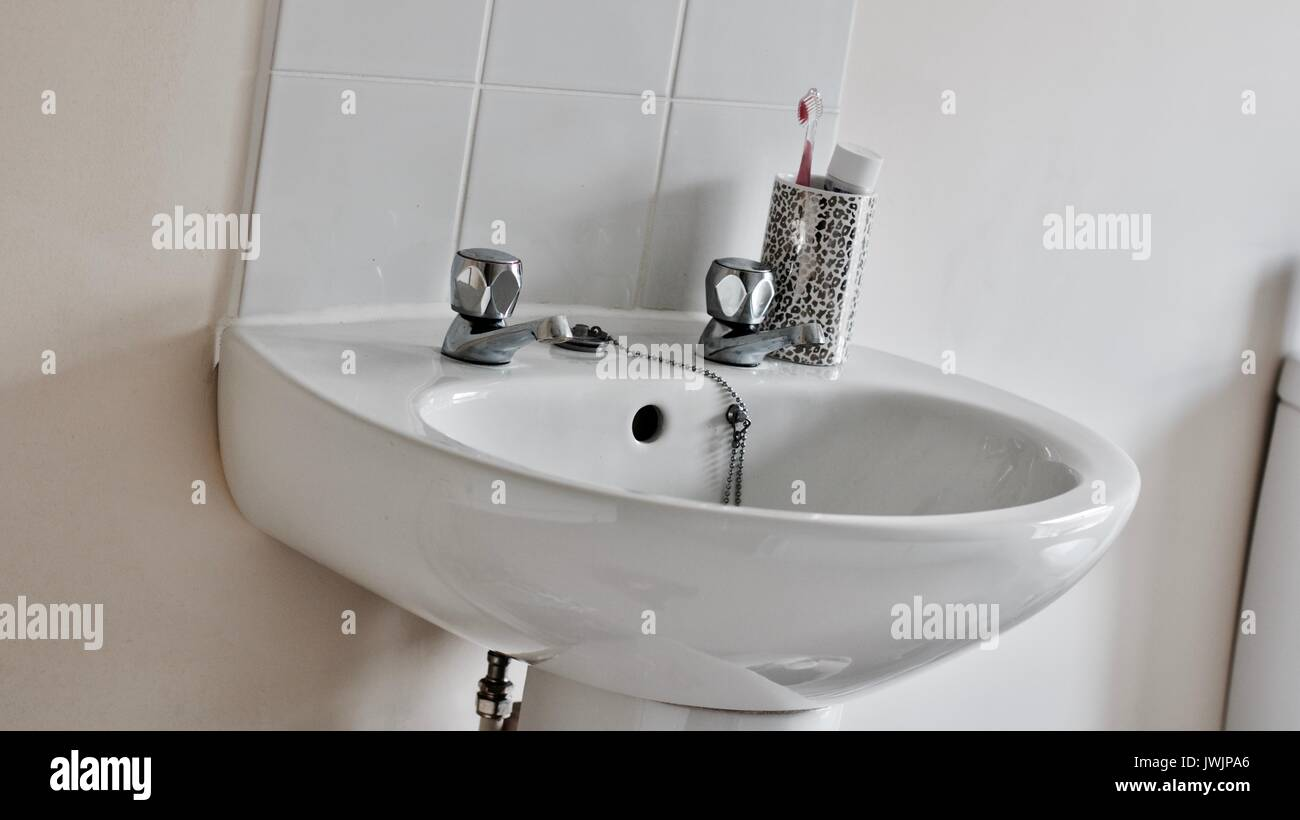 Small white sink in english toilet with two faucets near toothbrush ...