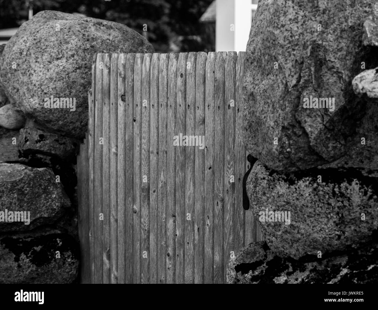 A b;ack and white image of a wooden gate flanked by gateposts of large granite rocks - Stock Image