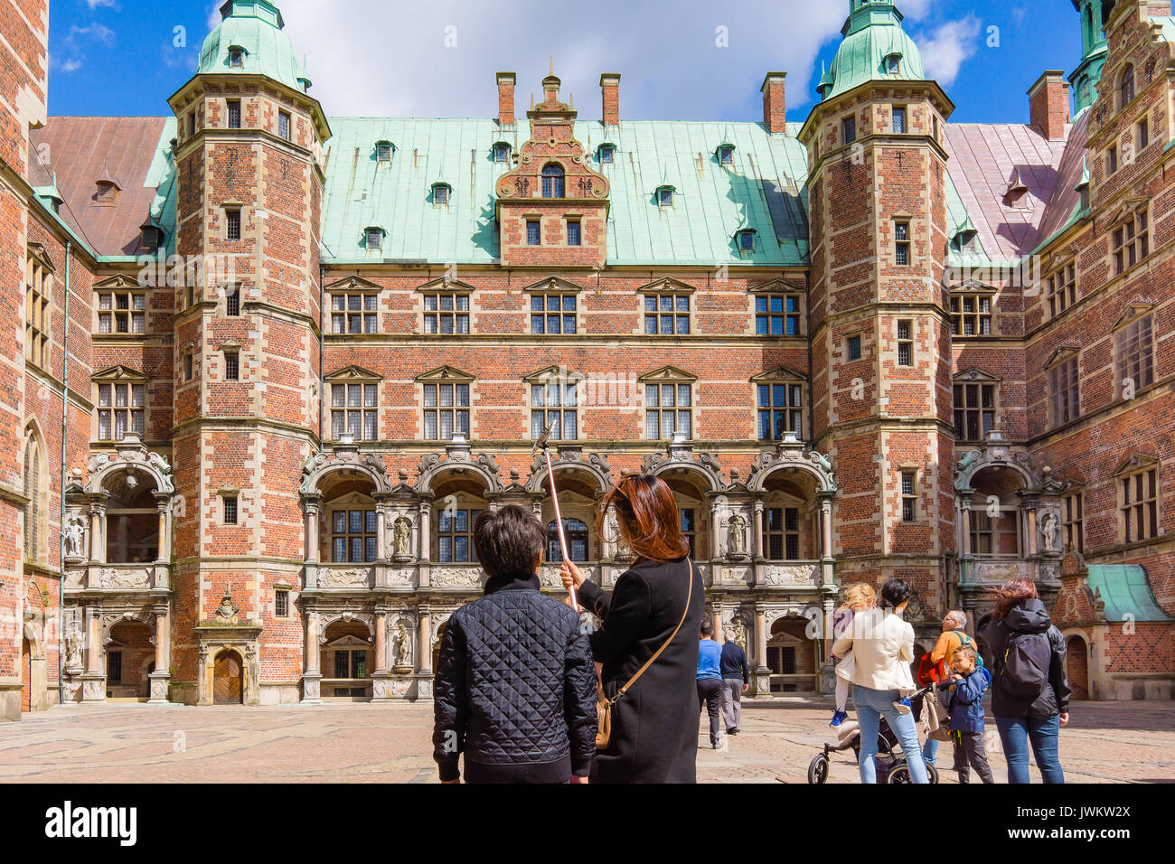 Mother and son using a selfie stick in front of the royal Frederiksborg castle, Tourists in the background. Hillerod, Denmark, August 6, 2017 - Stock Image