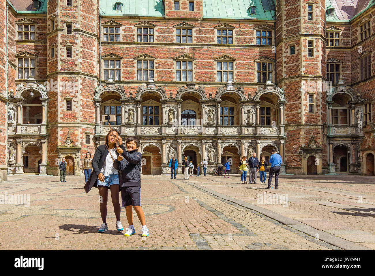 Asian turists in Denmark. Mother and son taking photo with a selfie stick in front of Frederiksborg castle, Hillerod, Denmark, August 6, 2017 - Stock Image